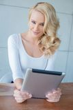 Beautiful young blond woman holding a tablet Royalty Free Stock Images