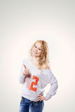 Beautiful young blond woman in jeans and t-shirt showing a thumbs up on. A white background Royalty Free Stock Image