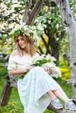 Beautiful young blond woman in lilac wreath on a swing royalty free stock image