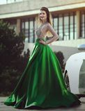 A beautiful young blond woman in a luxurious green evening dress near car. royalty free stock photography