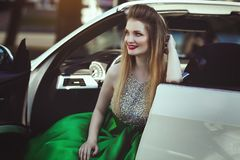 A beautiful young blond woman in a luxurious green evening dress is sitting in a car cabriolet. stock photos