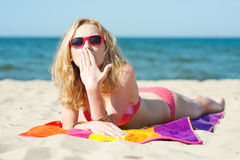 Beautiful young blond woman lying on a beach Stock Image