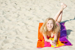 Beautiful young blond woman lying on a beach Royalty Free Stock Image