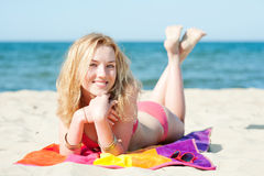 Beautiful young blond woman lying on a beach Royalty Free Stock Photos
