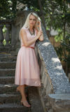 Beautiful young blond woman outdoors. Young blond woman in a pink dress outdoors stock photos