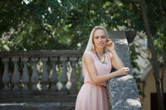Beautiful young blond woman outdoors. Young blond woman in a pink dress outdoors royalty free stock photo