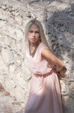 Beautiful young blond woman outdoors. Young blond woman in a pink dress outdoors stock photography