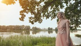 Beautiful young blond woman outdoors portrait near the lake. stock video footage