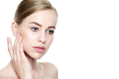 Beautiful Young Blond Woman with Perfect Skin touching her face. Facial treatment. Cosmetology, beauty and spa concept Stock Image