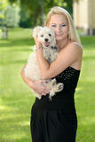 Beautiful young blond woman posing with her dog Royalty Free Stock Photo