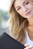 Beautiful Young Blond Woman Reading Folder or Menu Royalty Free Stock Photography