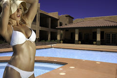 Beautiful young blond woman at resort hotel pool stock photo