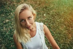 Beautiful young blond woman sits on the green grass and looks at the camera with beautiful gray eyes. Modern lifestyle royalty free stock image