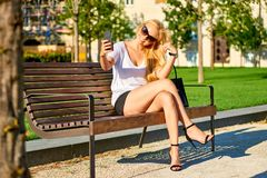 Young woman siting on a bench and taking selfies. A beautiful young blond woman sitting on a bench in the sunset and taking selfies with her smartphoner Royalty Free Stock Images