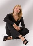 Beautiful young blond woman sitting in a black outfit. Full-length portrait of a beautiful young blonde woman sitting wearing a black outfit Stock Photography