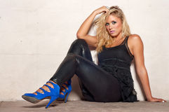 Beautiful young blond woman sitting on floor. Fashion concept image of beautiful club party girl sitting on sidewalk on a hot summers night Stock Images