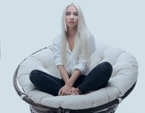 Beautiful young woman sitting on the couch in a large comfortable armchair. Beautiful young blond woman sitting in large comfortable armchair. photo with copy Royalty Free Stock Photos