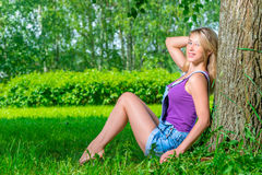Beautiful young blond woman  sitting near the tree Royalty Free Stock Photos