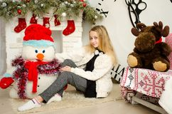 Beautiful young blond woman sitting in the new year with presents near the fireplace and snowman royalty free stock photo