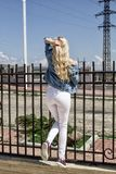 A beautiful young blond woman is standing with her back against the fence. stock photography
