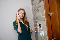 A beautiful young blond woman talking on the intercom Stock Photo