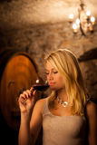 Beautiful young blond woman tasting red wine in a wine cellar Royalty Free Stock Photography