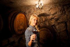 Beautiful young blond woman tasting red wine in a wine cellar Royalty Free Stock Photo