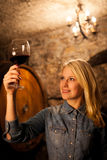 Beautiful young blond woman tasting red wine in a wine cellar Royalty Free Stock Images