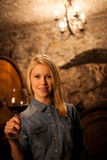 Beautiful young blond woman tasting red wine in a wine cellar Royalty Free Stock Photos