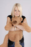 Beautiful young blond woman with teddy bear Stock Photography