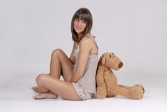 Beautiful young blond woman with teddy bear Royalty Free Stock Image