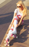 Beautiful young blond woman in a top sports pink shorts and vintage roller derby sits on a bench on a warm summer evening. view fr Royalty Free Stock Photos