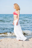 Beautiful young blond woman walking on a beach Royalty Free Stock Photography