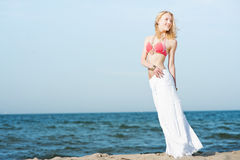 Beautiful young blond woman walking on a beach Royalty Free Stock Images