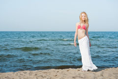 Beautiful young blond woman walking on a beach Stock Images