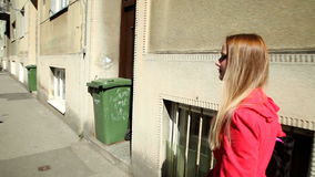 Beautiful young blond woman walking down the street stock footage