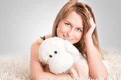 Beautiful young blond woman wearing pajamas. A beautiful young blond woman wearing pajamas and holding sheep toy Stock Image