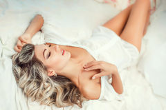Beautiful young blond woman. In white body basking in the morning in bed Royalty Free Stock Images