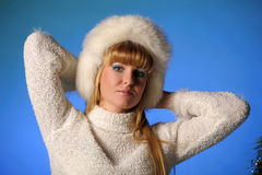 Beautiful young blond woman in a white fur hat Royalty Free Stock Photo
