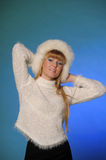Beautiful young blond woman in a white fur hat Stock Photography