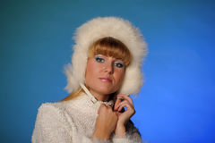 Beautiful young blond woman in a white fur hat Royalty Free Stock Photography