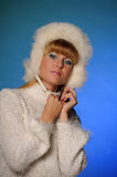 Beautiful young blond woman in a white fur hat Royalty Free Stock Image