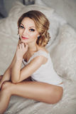 Beautiful young blond woman in white lingerie Stock Photo