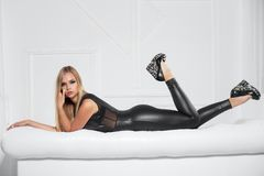 Beautiful young blonde. Posing in the studio dressed in a black leather suit royalty free stock photo