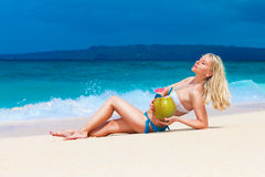 Beautiful young blonde in bikini is lying on a tropical beach wi. Th coconut royalty free stock photography