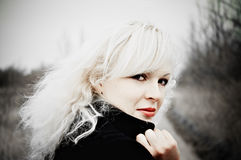 Beautiful young blonde in black coat. Half-turned Royalty Free Stock Images