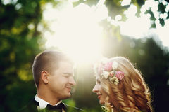 Beautiful young blonde bride and handsome groom at sunset in the Royalty Free Stock Photography