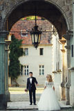 Beautiful young blonde bride walking to handsome wealthy groom u Royalty Free Stock Photography