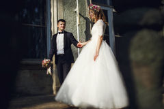 Beautiful young blonde bride in white dress with handsome groom Stock Images