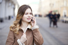 Beautiful young blonde calling by phone Royalty Free Stock Photos